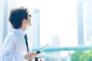携帯電話を持ち遠くを見つめるビジネスマンの写真素材 [FYI01572471]