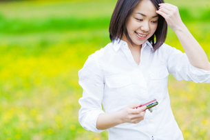 デジカメを持って花畑に立つ日本人女性の写真素材 [FYI01572473]