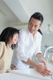 皿を洗う父親と笑顔の娘の写真素材 [FYI01572569]