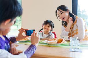 テーブルを挟んで写真を撮る2組の母と子の写真素材 [FYI01572586]