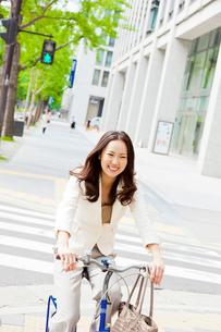 自転車に乗るビジネスウーマンの写真素材 [FYI01572642]