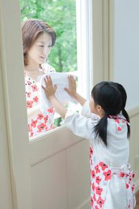 窓拭きをする日本人の母と娘の写真素材 [FYI01572649]