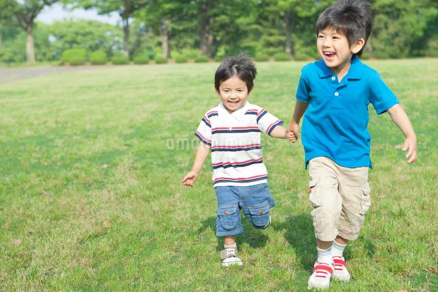 手を繋いで走る日本人兄弟の写真素材 [FYI01572663]