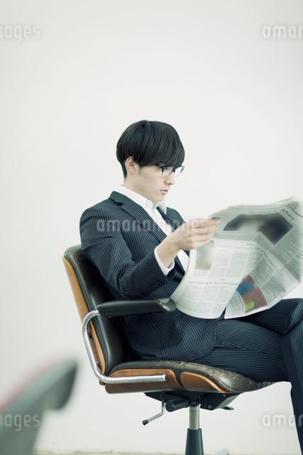 椅子に座り新聞を読むビジネスマンの写真素材 [FYI01572802]