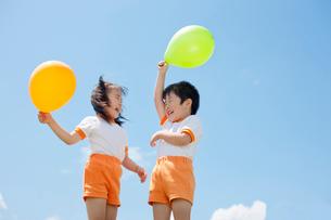 風船を持って遊ぶ体操服姿の幼稚園児の写真素材 [FYI01572850]