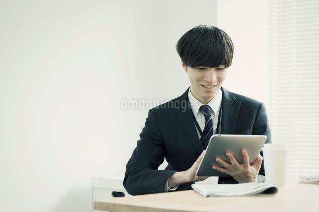 タブレットPCを操作するビジネスマンの写真素材 [FYI01572913]