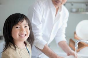 皿を洗う父親と笑顔の娘の写真素材 [FYI01572971]