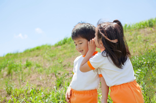 耳打ちをする体操服姿の幼稚園児の写真素材 [FYI01572979]