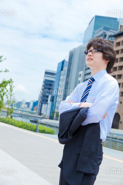 上着を脱いで腕組みをする日本人ビジネスマンの写真素材 [FYI01572997]