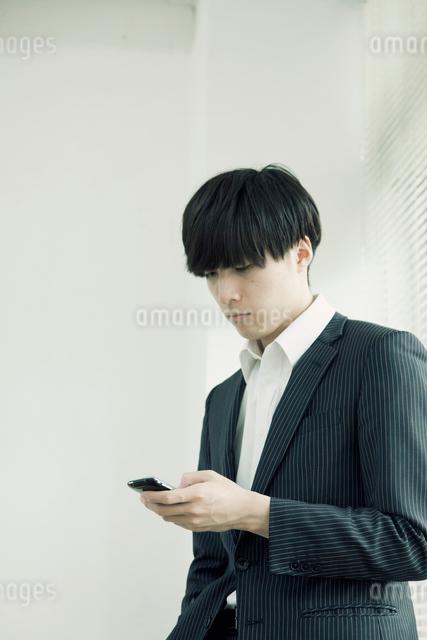 スマートフォンを操作するスーツ姿の男性の写真素材 [FYI01573009]