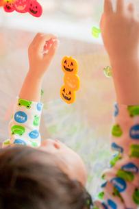 窓にハロウィンのシールを貼る男の子の写真素材 [FYI01573061]