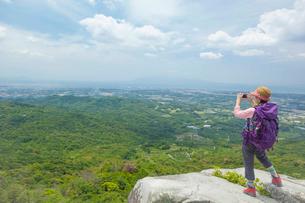 岩の上に立ち写真を撮るトレッキングの女性の写真素材 [FYI01573072]