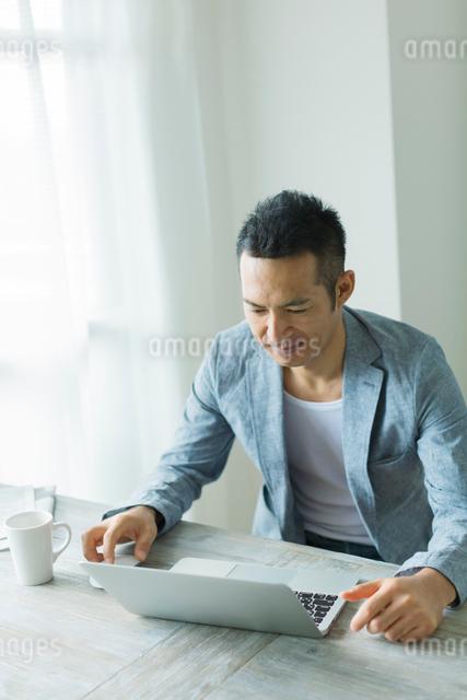 ノートパソコンに向かう男性の写真素材 [FYI01573117]