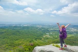 岩の上に立ち背伸びをするトレッキングの女性の写真素材 [FYI01573122]