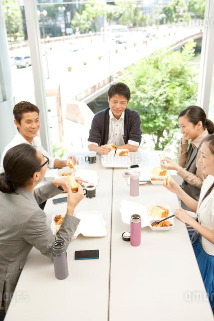 テーブルを囲みランチを食べる男女の写真素材 [FYI01573172]