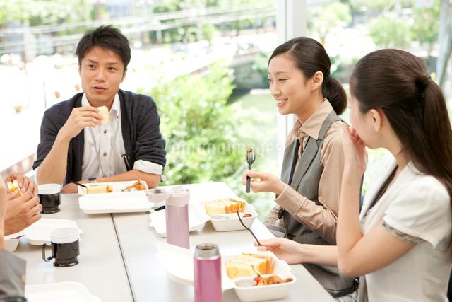 テーブルを囲みランチを食べる男女の写真素材 [FYI01573252]