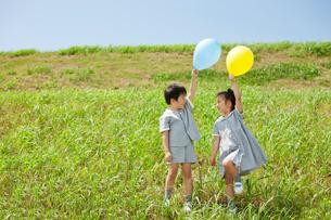 草原で風船を持って立つ2人の幼稚園児の写真素材 [FYI01573306]