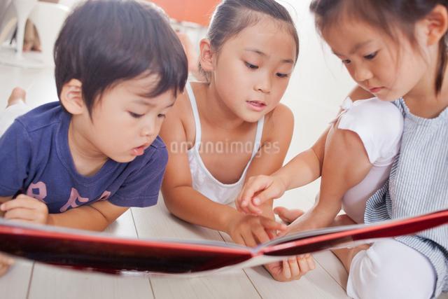 本を読む3人の子供達の写真素材 [FYI01573478]