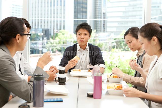 テーブルを囲みランチを食べる男女の写真素材 [FYI01573576]