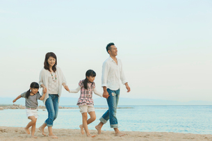 海辺を歩く日本人家族の写真素材 [FYI01573589]