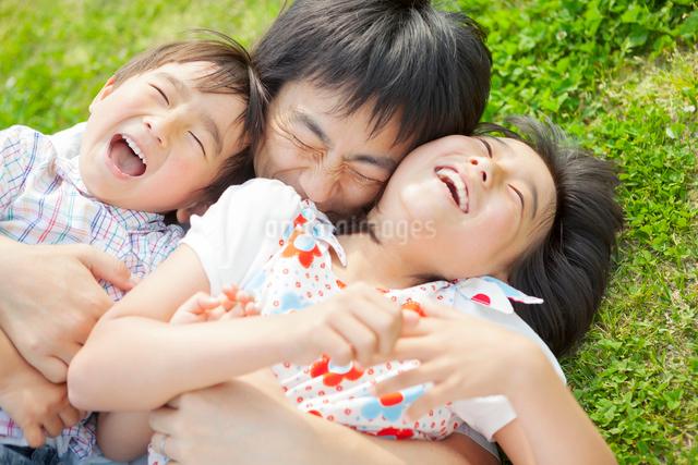 寝転んで抱きつく親子の写真素材 [FYI01573721]