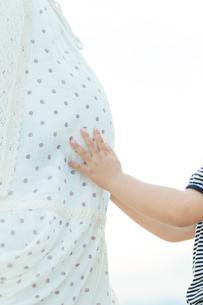 妊婦の母のお腹を触る娘の手元の写真素材 [FYI01573801]