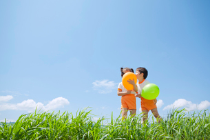 風船を持ち草原に立つ体操服姿の幼稚園児の写真素材 [FYI01573804]
