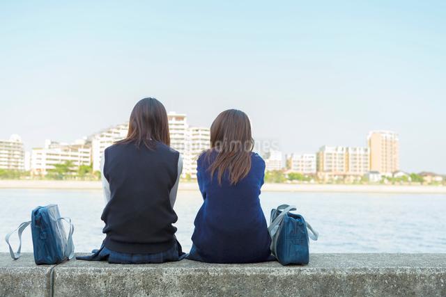 防波堤に座る2人の日本人女子高生の写真素材 [FYI01573809]
