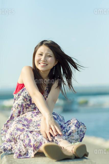 防波堤に座る日本人女性の写真素材 [FYI01573928]