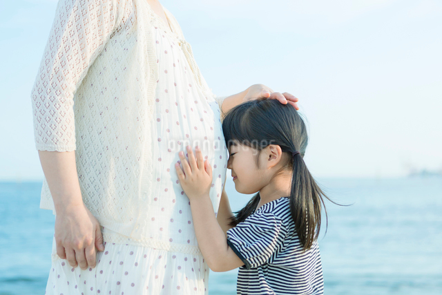 妊婦の母のお腹に顔をつける娘の写真素材 [FYI01574353]