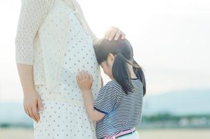 妊婦の母のお腹に顔をつける娘の写真素材 [FYI01574360]