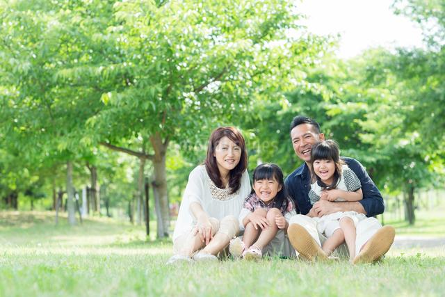 新緑の公園に座る日本人家族の写真素材 [FYI01574553]