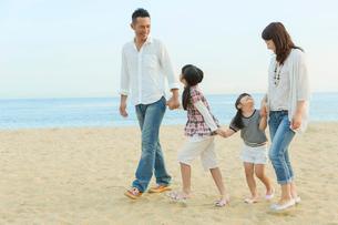 海辺を歩く日本人家族の写真素材 [FYI01574831]