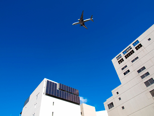 ソーラーパネルと青空と飛行機の写真素材 [FYI01585466]