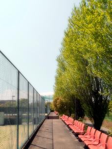 オレンジのイスとテニスコートのフェンスの写真素材 [FYI01585617]