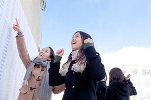 合格発表板の前で喜ぶ女子学生の写真素材 [FYI01594222]