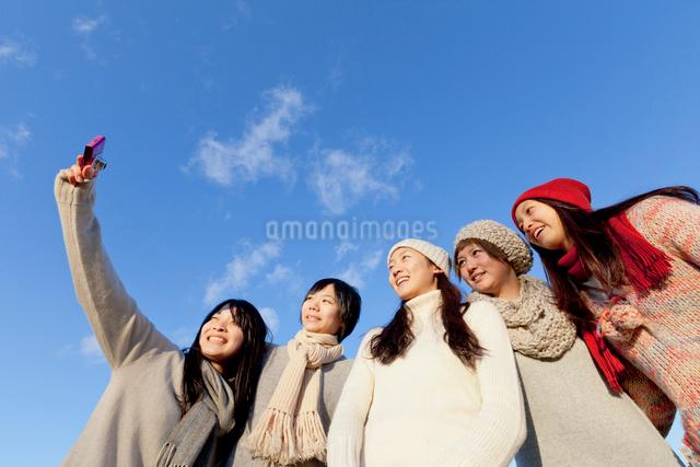 青空と写真を撮る女子学生達の写真素材 [FYI01594335]
