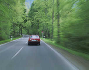森を走り抜ける車の写真素材 [FYI01594346]