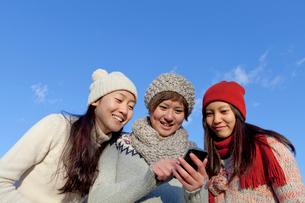 スマートフォンを覗き込む3人の女性の写真素材 [FYI01594719]