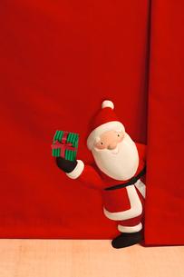 赤い幕から顔を出すプレゼントを持ったサンタクロースの写真素材 [FYI01596269]