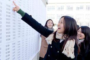 合格発表板の前で喜ぶ女子学生の写真素材 [FYI01596674]