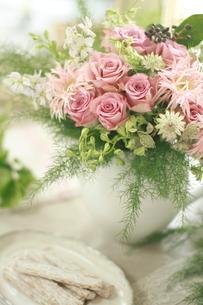 ピンクのバラの花アレンジと皿に乗せた菓子の写真素材 [FYI01597138]