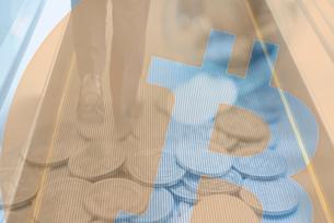 ビジネスマンの足元とまき散らした硬貨,ビットコインロゴマークの合成の写真素材 [FYI01597378]