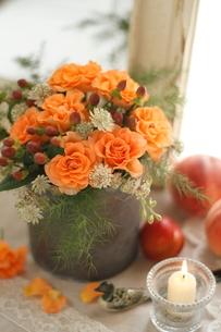 オレンジのバラの花アレンジと鏡とキャンドルの写真素材 [FYI01597569]