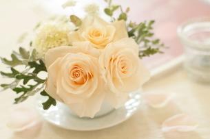 コーヒーカップに挿した花アレンジメントとキャンドルホルダーの写真素材 [FYI01597833]