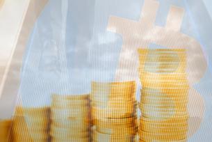 ビジネスマンの足元と空と雲,積み重ねた硬貨,ビットコインロゴマークの合成の写真素材 [FYI01597842]