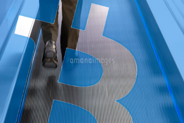 ビジネスマンの足元,ビットコインロゴマークの合成の写真素材 [FYI01598107]