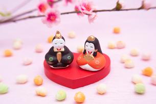 ハート型の台に乗った雛人形と桃の花,ひなあられの写真素材 [FYI01598328]