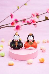 桃色の台に乗った雛人形と桃の花,ひなあられの写真素材 [FYI01598371]