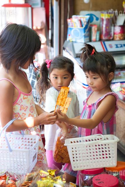 駄菓子屋で買い物をする女の子たちの写真素材 [FYI01598425]